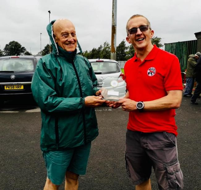 WINNERS: Bury men's team captain Byron Edwards is awarded the champion's trophy by North of England Track and Field League secretary Alan Johnson