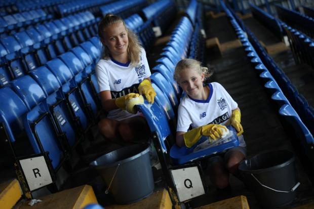 Bury FC fans Ella and Millie Smith help clean up the stadium.
