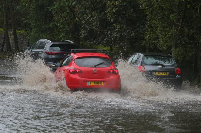 Drivers take on flooded roads after heavy rain in Bolton. Photo: Phil Taylor