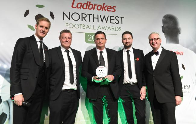 Mark Litherland, second from left, and Ryan Kidd, centre, pick up the award on behalf of Bury