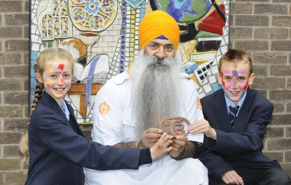 Pupils Emily Kay and Jordan Astley, both aged 11, meet Roop Singh, holding the One God symbol. The children had their faces painted Hindu style