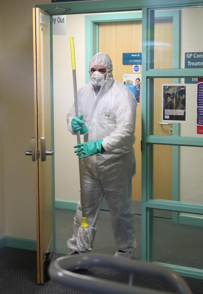 RETRANSMITTING PIXELATING DOOR LABELA man in protective clothing cleaning the County Oak Medical Centre GP practice in Brighton which has been temporarily closed
