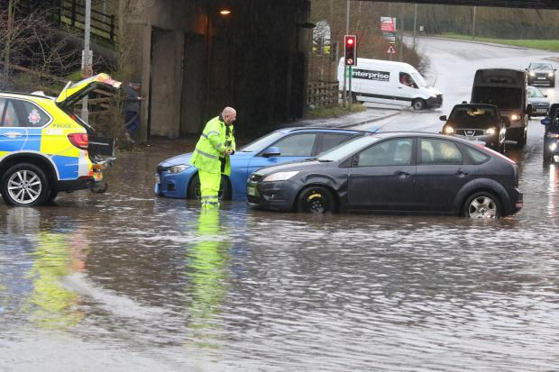 Bury Times: Emergency services help cars after they come to standstill in flooding at the M66 junction. Picture, Phil Taylor