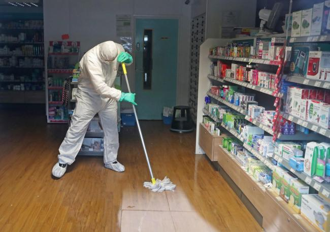 A man in protective clothing cleaning the County Oak Medical Centre GP practice in Brighton which has been temporarily closed