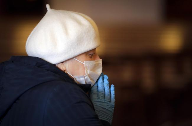 A Catholic believer, wearing a face mask and gloves to protect from coronavirus, prays in a church as religious services continue in Minsk, Belarus, Saturday, April 11, 2020. The Catholic community in predominantly Orthodox Christian Belarus prepare to ce