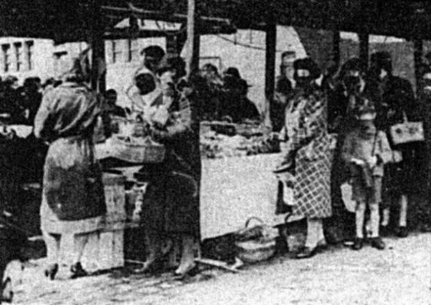 Bury Times: Women and children wearing gas masks as they carry on their shopping at Bury Market in a gas test during the Second World War