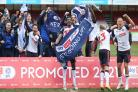 Wanderers celebrate promotion after victory at Crawley on the final day of the season.