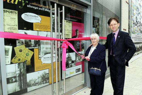 MEMORIES ARE MADE OF THIS: Flo Leeming cuts the ribbon outside the heritage project shop, watched by David Laycock