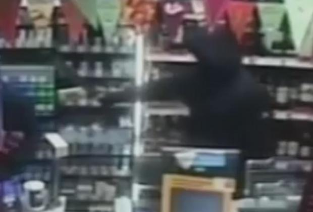 Bury Times: Still of machete-wielding thug caught on CCTV at Over Hulton Co-op
