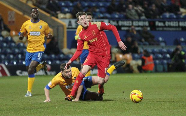 FLOORED Bury goalscorer Danny Mayor leaves Mansfield Town's John Dempster on the ground during the first half at Field Mill