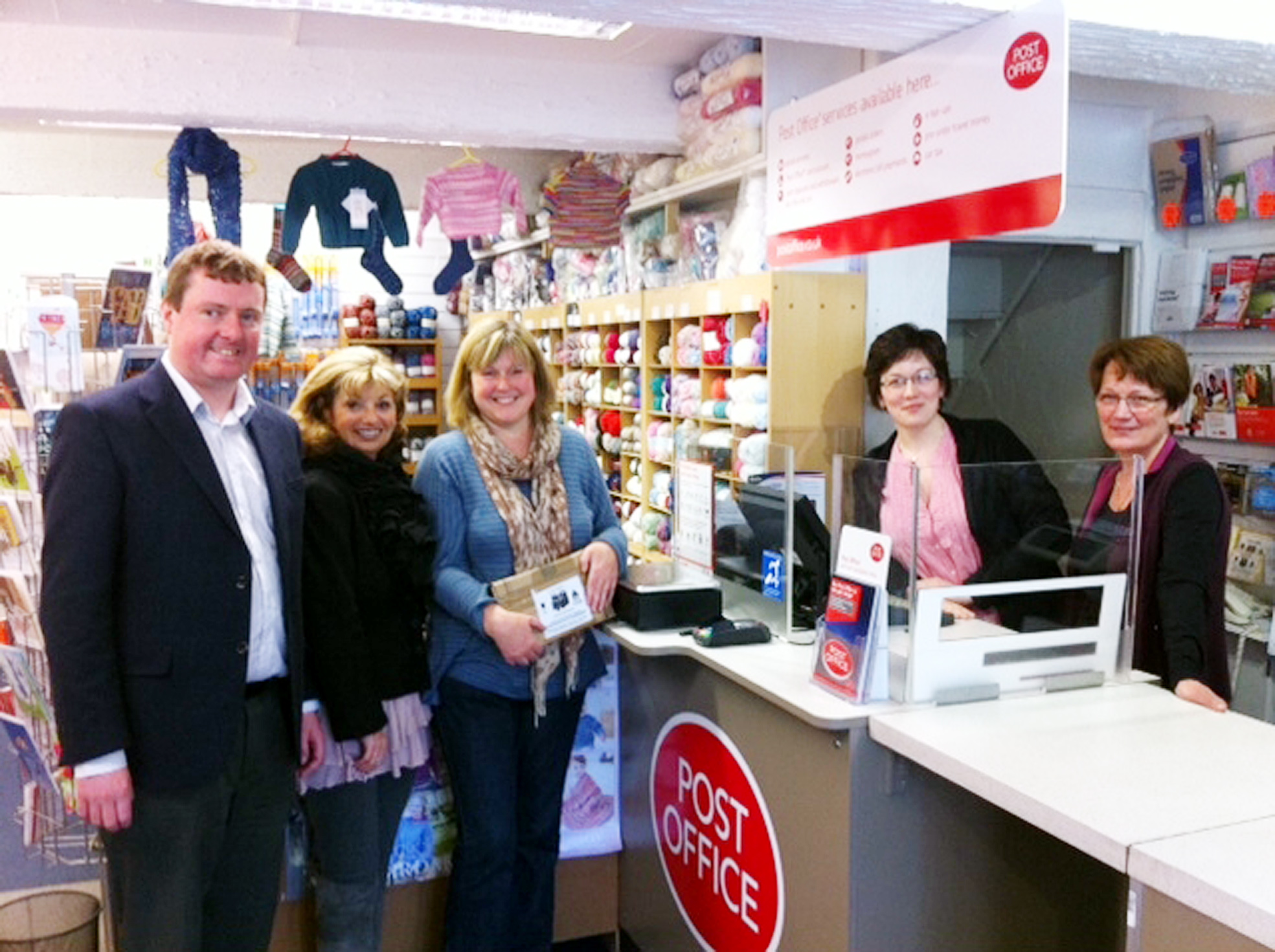 From  left, Cllr Iain Gartside, Cllr Yvonne Wright, and Judith Kelly, are some of the first customers at the new post office being run by Clare Brierley and Alison Baker, behind the counter