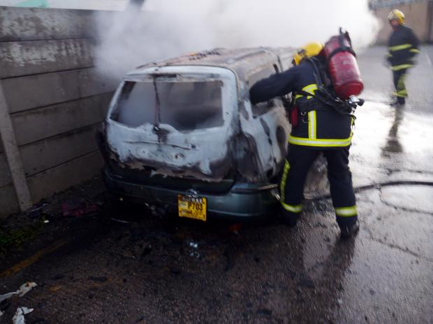 A firefighter deals with the car fire in Woolfold Industrial Estate, Elton