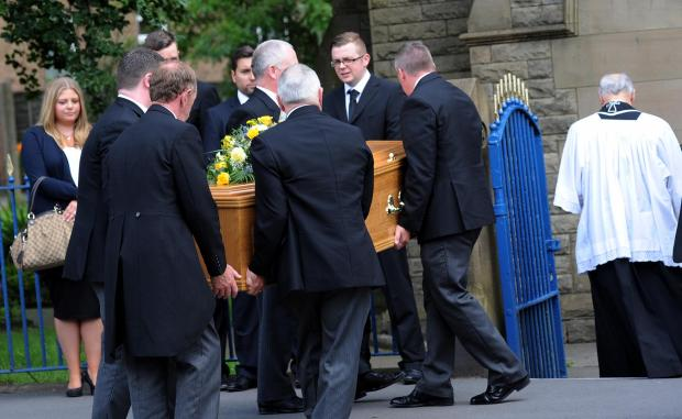 Bury Times: Family and friends carry the coffin of Eric Warburton into the church