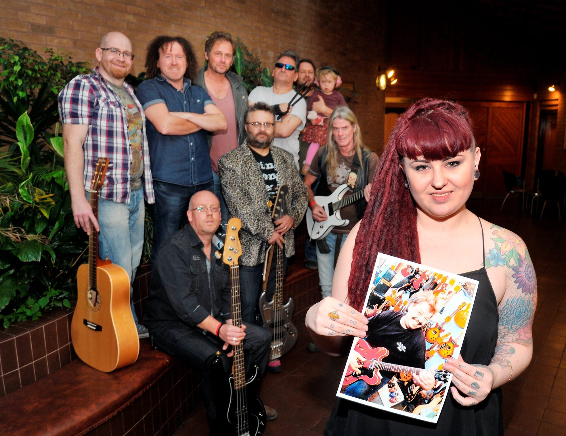 Daughter Emma Hand with a picture of her father Keith Hand and some of the band members that took part