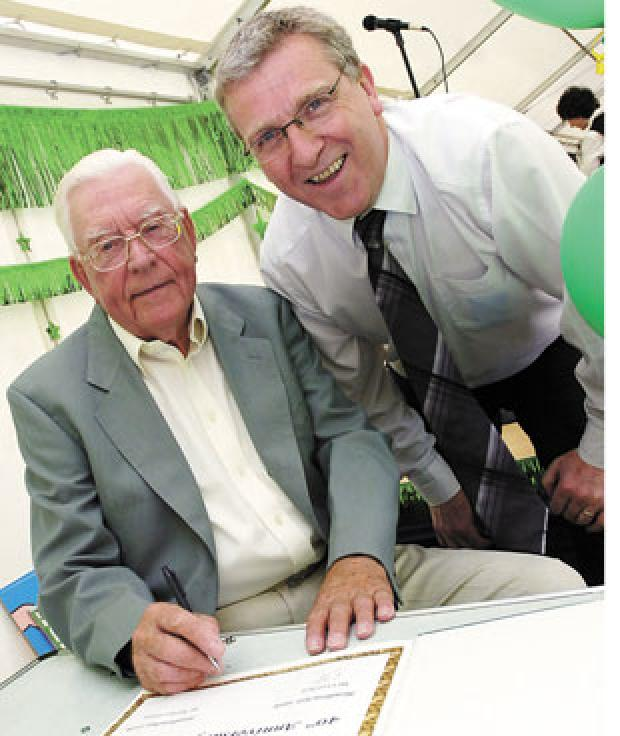 Bury Times: Greenhill's first headteacher Cyril Bell (left), signs the memories book, with present head, Martyn Pilling