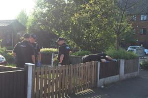 Police carrying out a search of a street with officers seen combing gardens