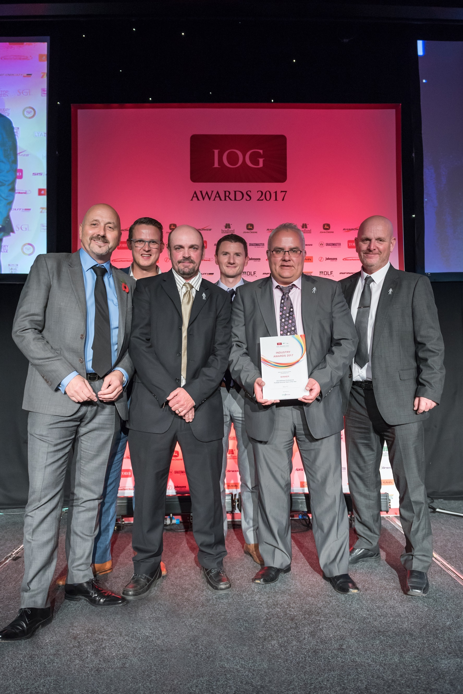 BBC presenter Mark Clemmit, left, hands over the award to Bury's groundstaff
