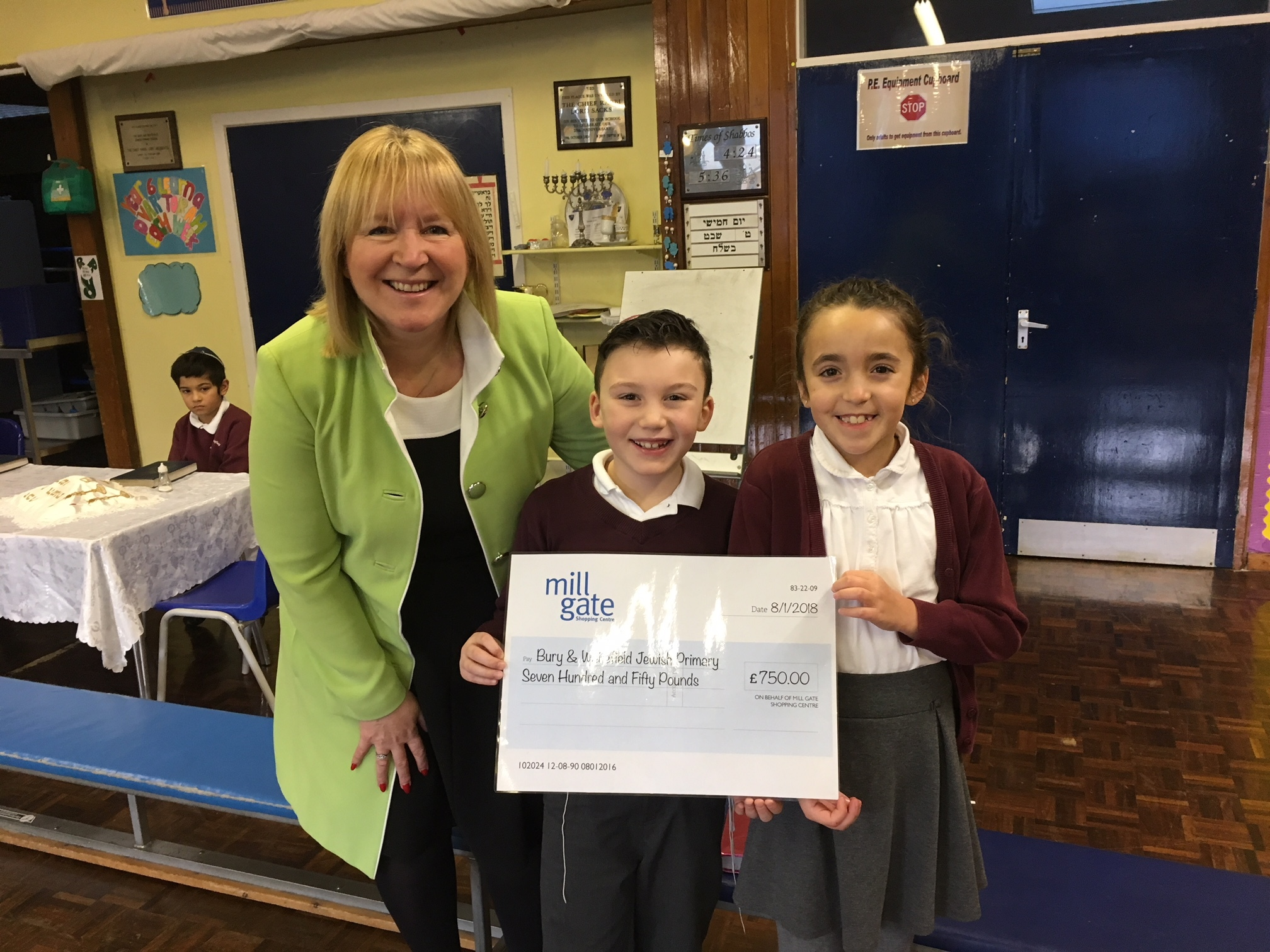 WIN: Rafi Radnor and Alessandra Guerini accept the cheque on behalf of the school from Mill Gate's manager Marie Gribben