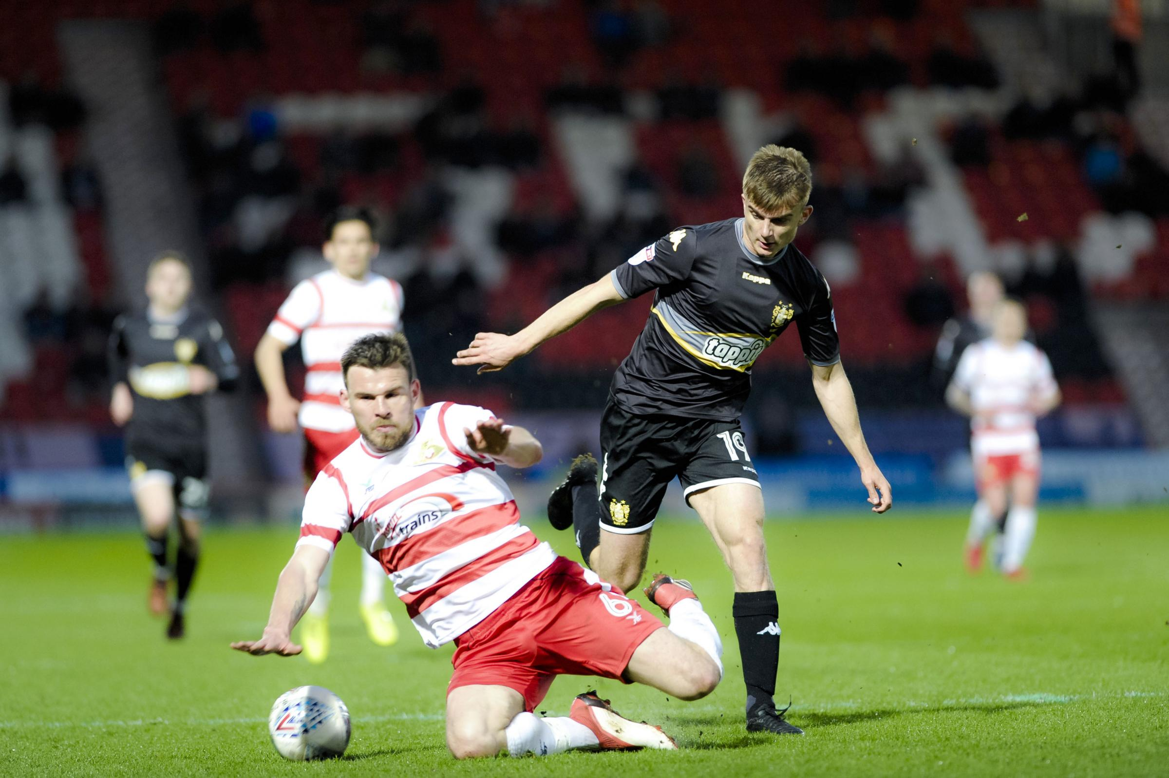 GOING FOR IT: Bury's George Miller challenges Doncaster defender Andrew Butler during last night's match