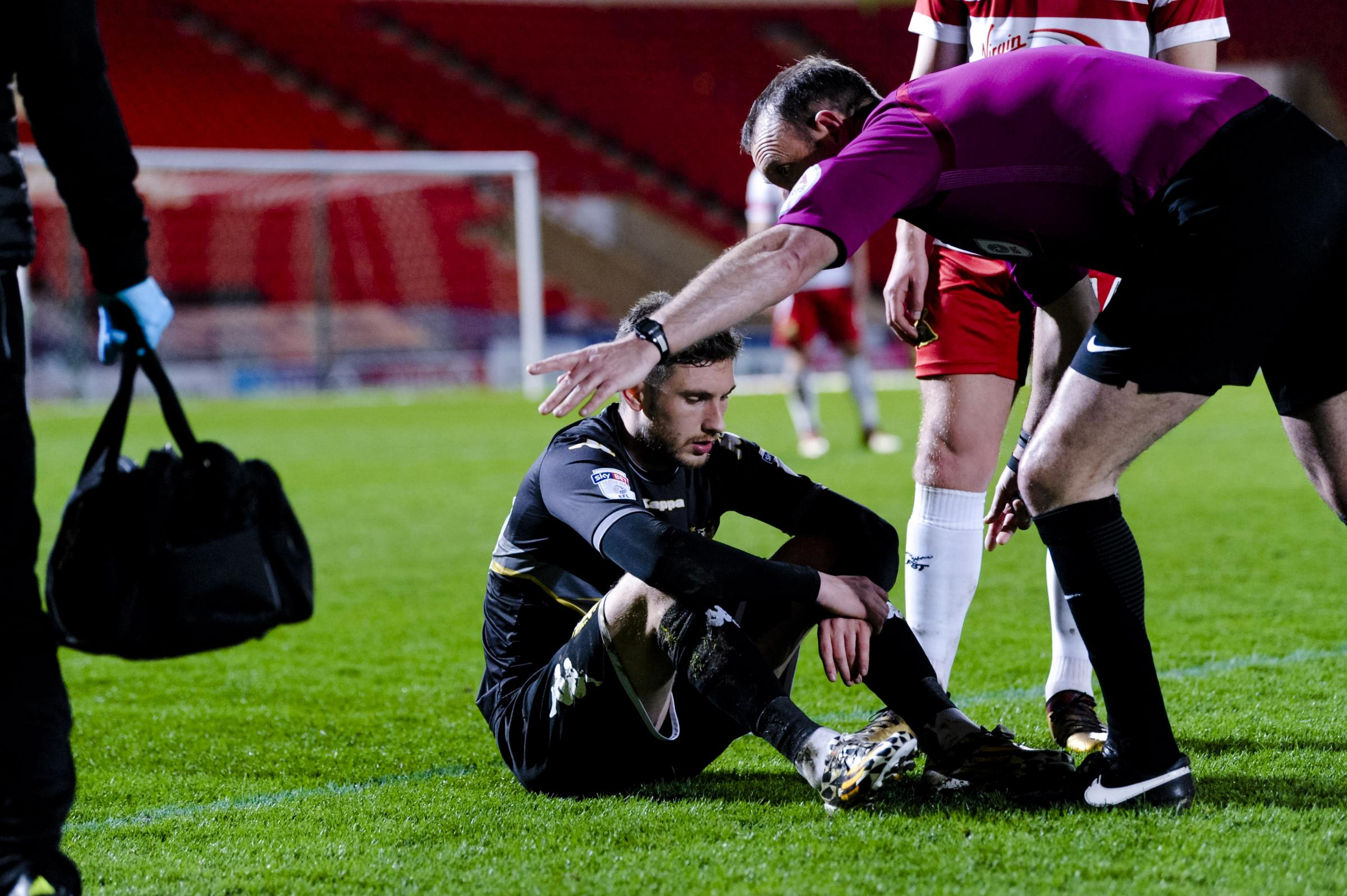 GLUM: Danny Mayor sums up Bury's season as he sits injured at Doncaster on Tuesday night. Picture by Andy Whitehead