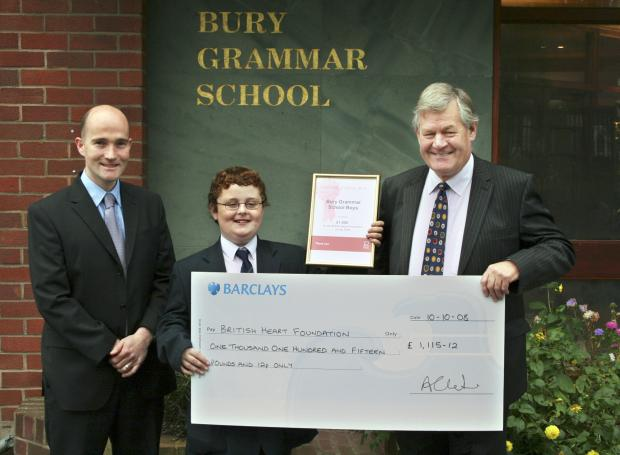 Bury Times: John Brown, right, from the British Heart Foundation, receives the cheque from Devin Cassidy, head of year, and pupil Nathan Brody