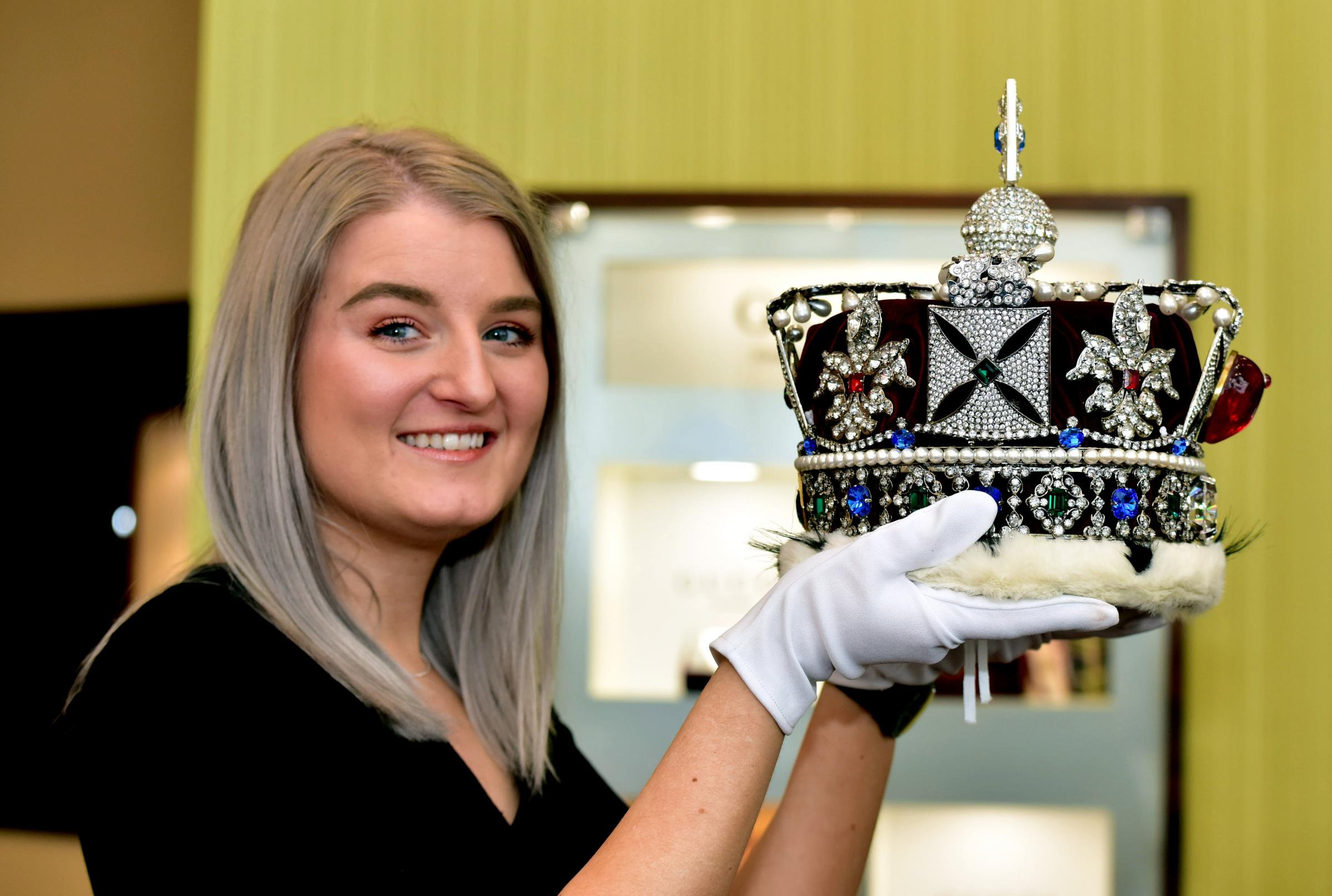 Charliee Dart, Supervisor at Peter Jackson the Jeweller, Bury with one of the replica crowns.