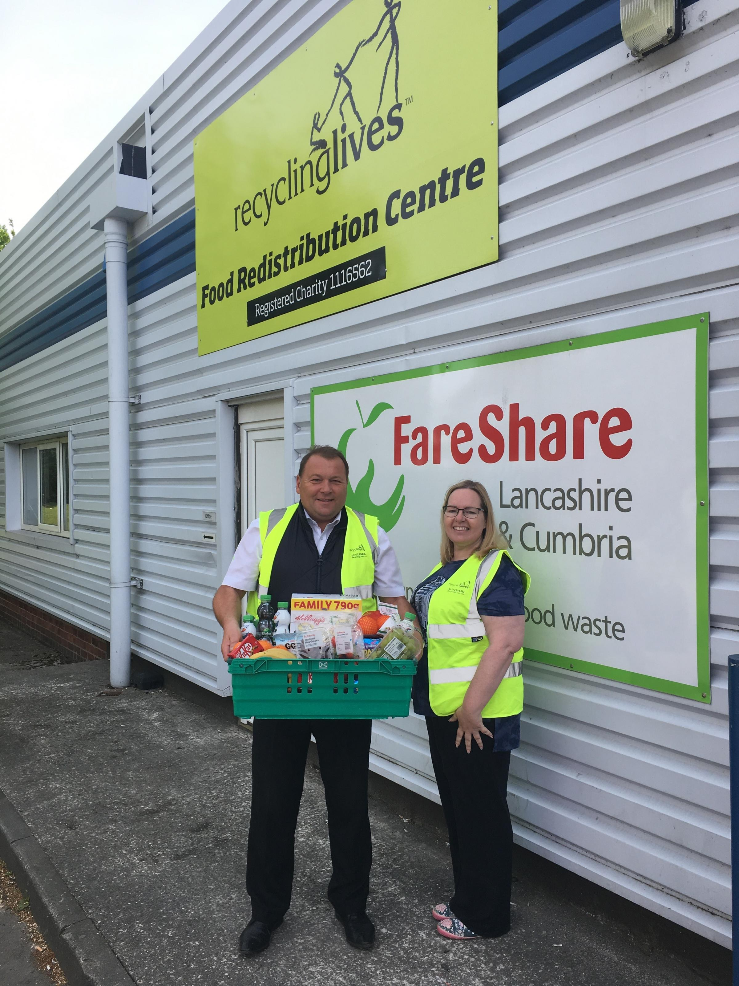 Lowercroft Primary School parent, Vicky Hilton, collects the hamper from head of charity Neil Flanagan at Recycling Lives' Food Redistribution Centre