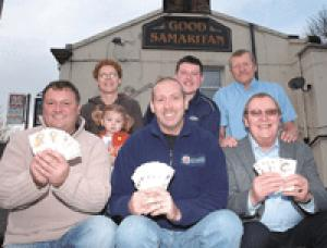 Tony Burke from Bury Hospice, Andy Roberts from Greater Manchester Fire Service, and Dave Galway of Peel Lions (front row) collect the cash from fundraisers Tracy, Leah and Duncan Ingam and licensee Roger Howarth (centre)