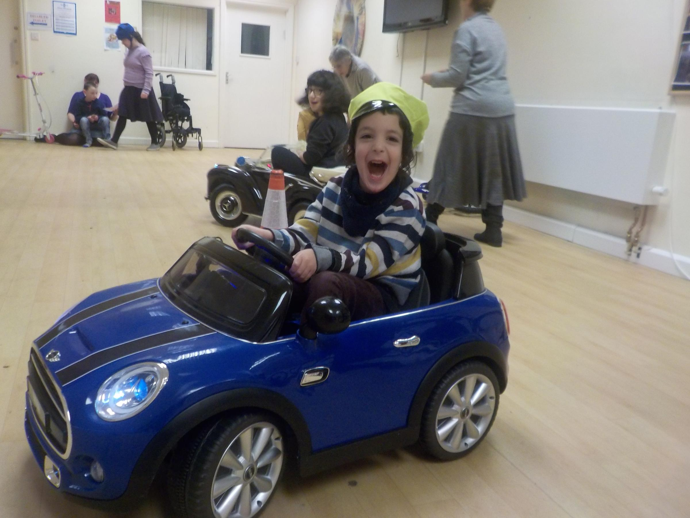 Youngster speeds around in an electric car at The Fed