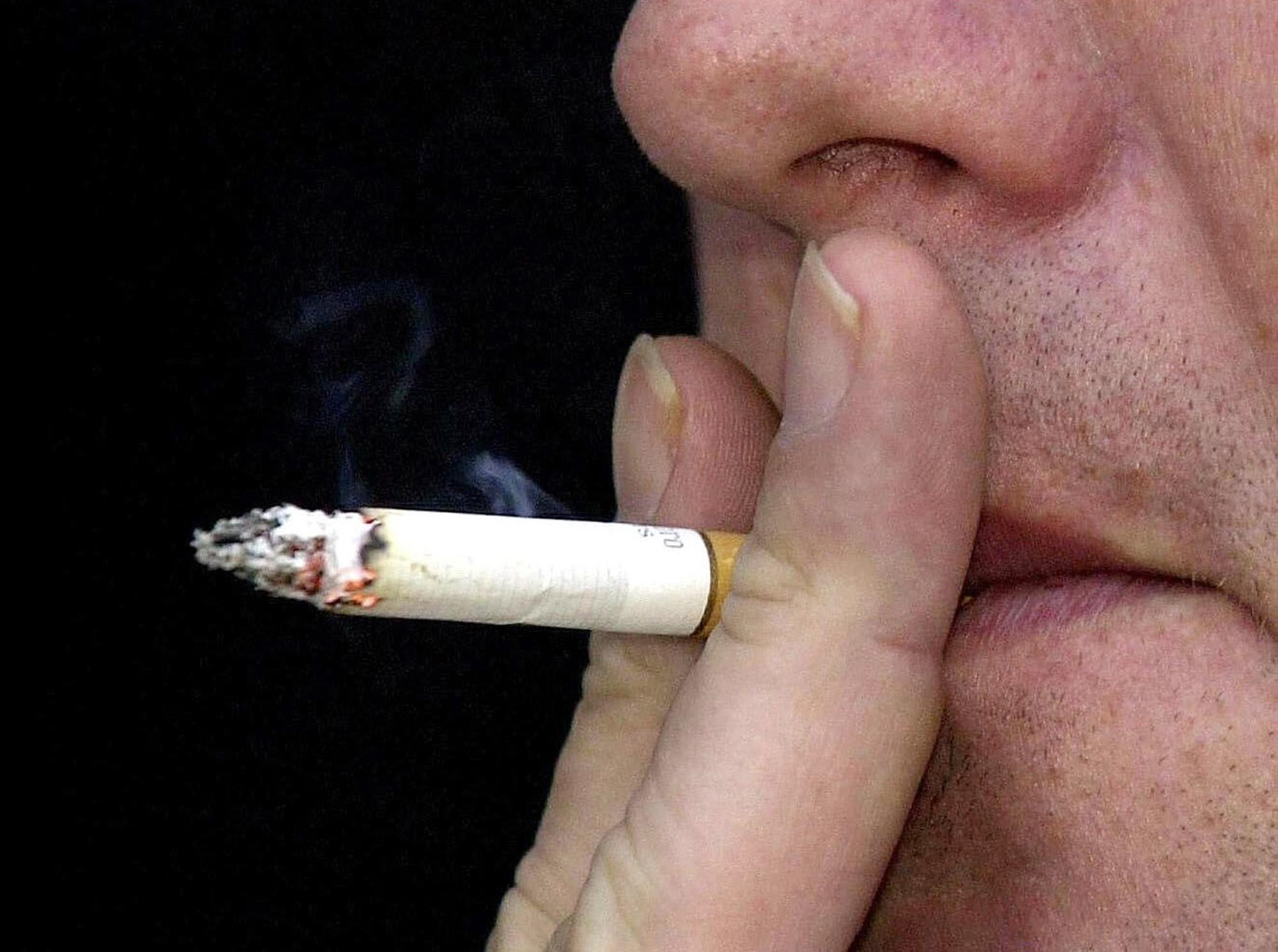 PA file photo dated 23/02/2004 of a smoker. Cigarette smoke has been voted the nation's worst household smell in a survey published, Tuesday February 1, 2005. In the research, 26% said smoke was the stink most likely to get up their noses. It came jus