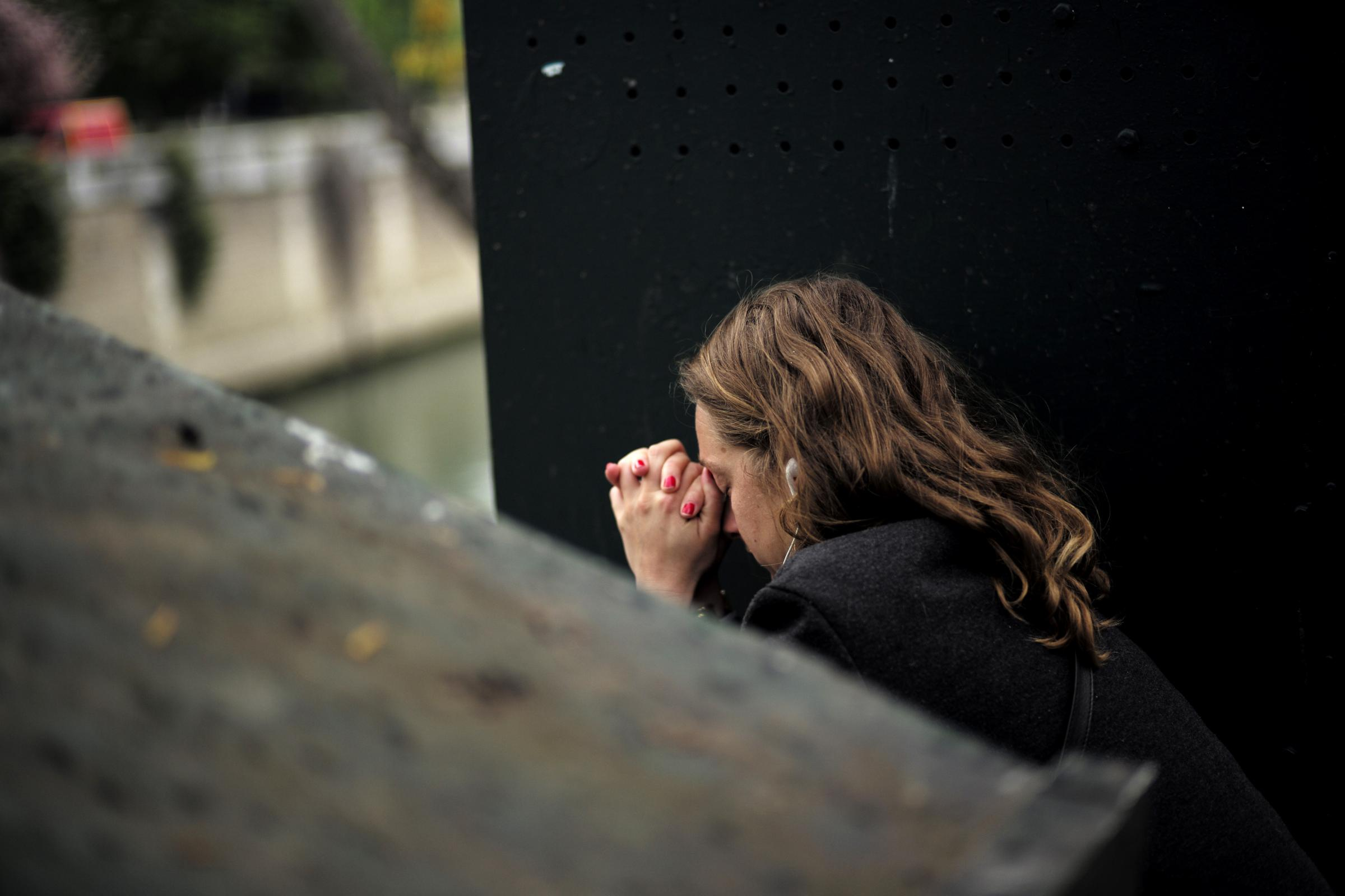 A woman prays near Notre Dame