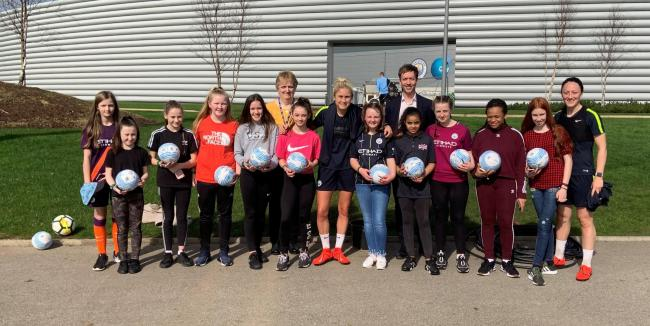 Pupils from St Monica's RC High School girl's football team with players from the Manchester City women's team