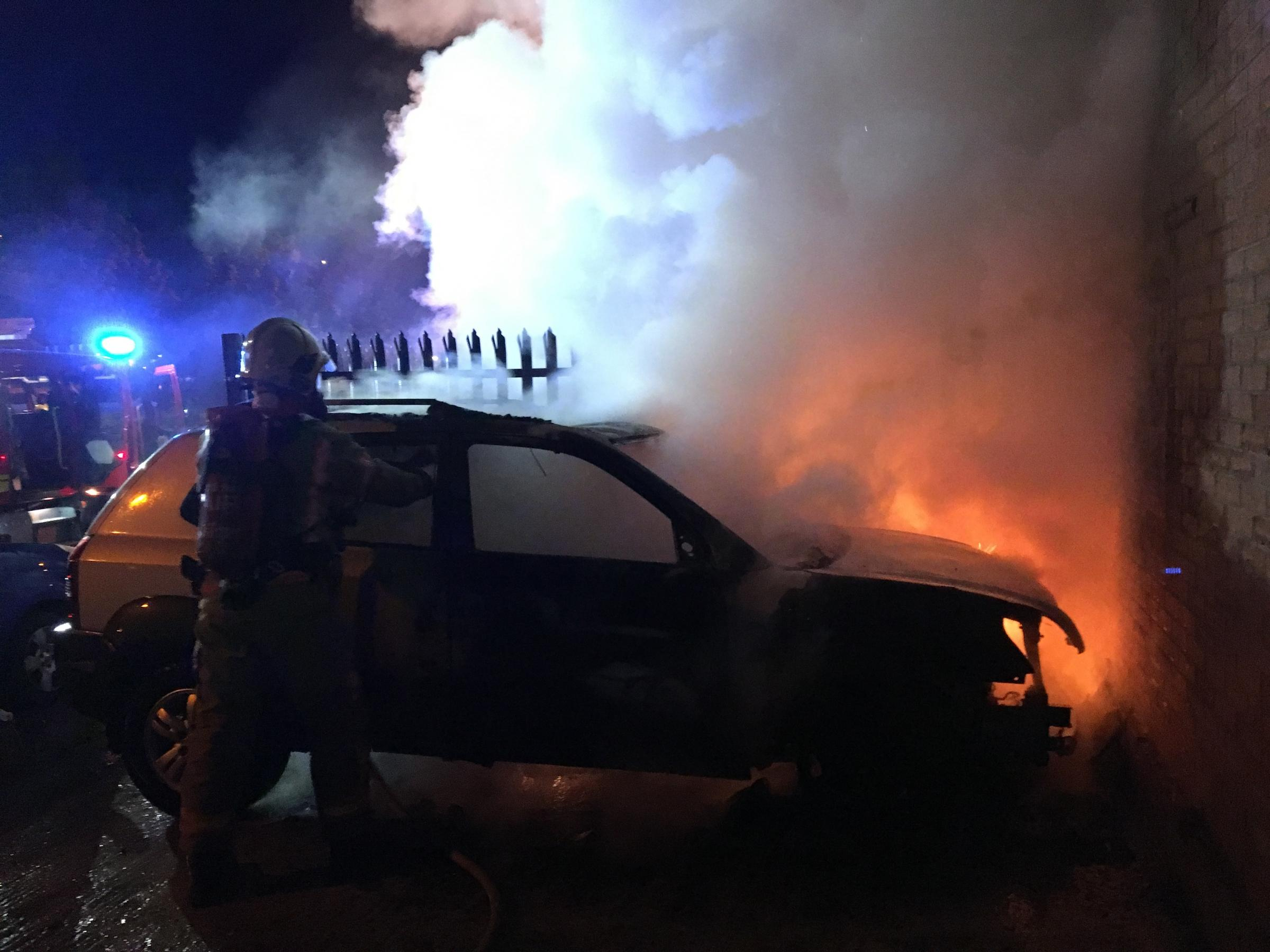 A firefighter wearing breathing apparatus helps extinguish the burning car